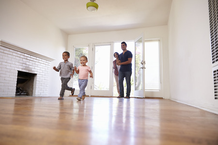 new years day: Excited Family Explore New Home On Moving Day Stock Photo