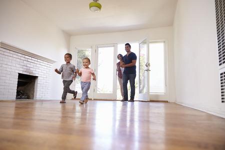 Upphetsad familj Utforska nytt hem på flyttningsdagen Stockfoto