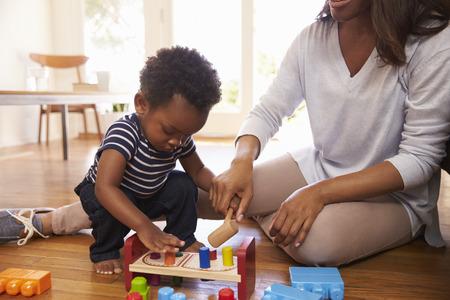 母と息子の自宅の床におもちゃで遊んで