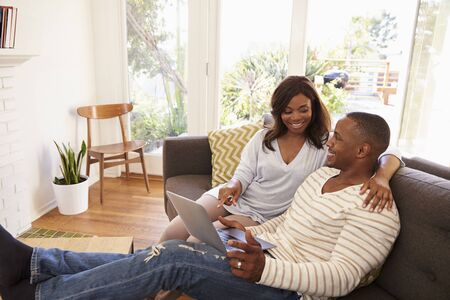 african america: Couple Relaxing On Sofa At Home Using Laptop Stock Photo