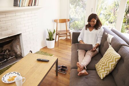 african america: Woman Relaxing On Sofa At Home Using Laptop