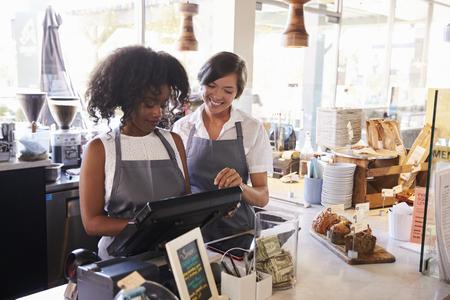 Novo empregado recebe treinamento na Delicatessen Checkout Imagens