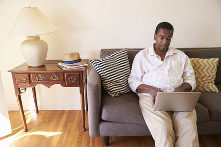 african america: Senior Man Sitting On Sofa At Home Using Laptop
