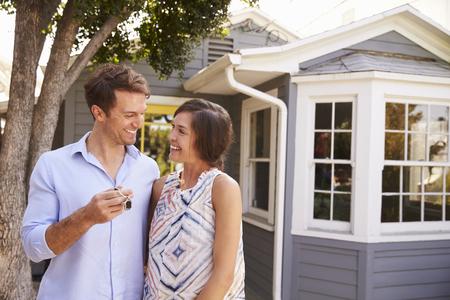 カップルは新しい家の外に立っているキー