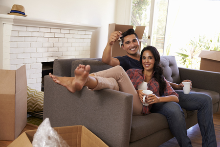 moving in: Couple On Sofa Holding Keys Taking A Break On Moving Day Stock Photo