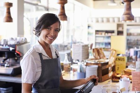 Portret van vrouwelijke werknemer die bij Delicatessen Afrekenen Stockfoto