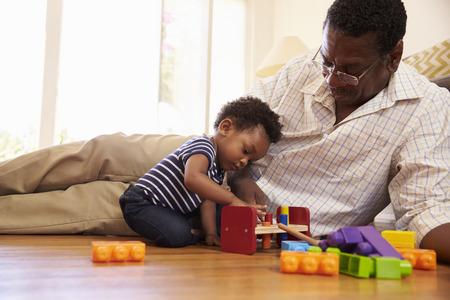 할아버지와 손자 집에서 바닥에 장난감을 가지고 노는 스톡 콘텐츠 - 71273376