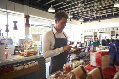 tiendas de comida: Empleado En Charcutería Comprobación de la tableta Con Digital Foto de archivo