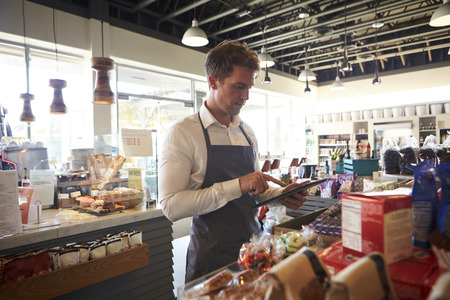 Werknemer In Delicatessen controleren Stock met digitale tablet