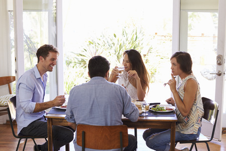 dinner food: Group Of Friends Enjoying Dinner Party At Home Together Stock Photo