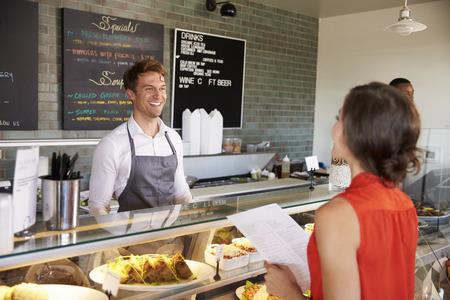 Man Werken Achter Teller In Delicatessen Met Voedsel Bestelling