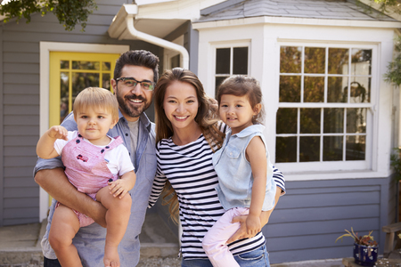 Portrait Of Excited Family Standing Outside New Home