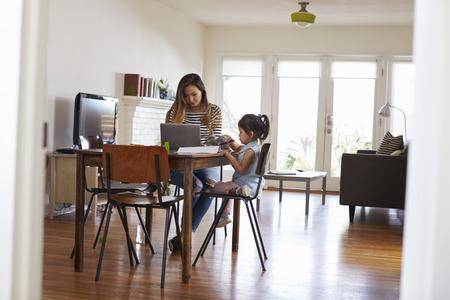 madre trabajando: La madre trabaja en la computadora portátil como la hija Llama la Imagen en libro Foto de archivo
