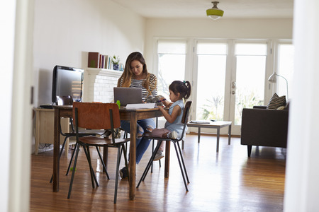 madre trabajando: Mother Works On Laptop As Daughter Draws Picture In Book