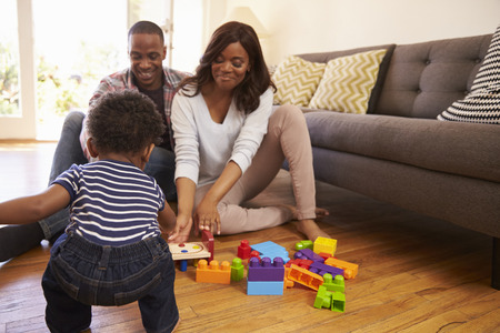 juguetes antiguos: Padres e hijo jugando con juguetes en el suelo en casa