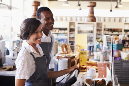 checkout: Staff Serving Customers At Delicatessen Checkout