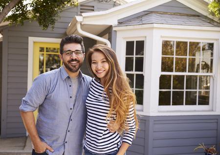 新しい家の外に立って興奮してカップルの肖像画