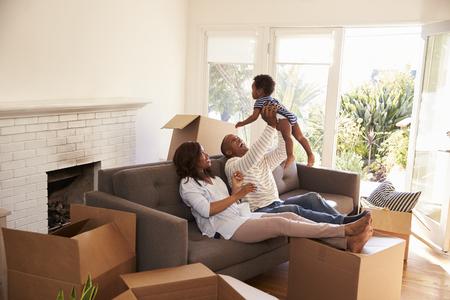 Los padres toman una rotura en el sofá con el hijo en el día que se mueve
