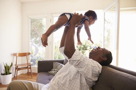 Abuelo y nieto jugando al juego en el sofá en casa