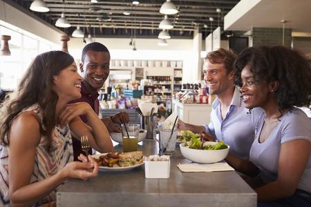 comidas: Friends Enjoying Lunch Date In Delicatessen Restaurant Foto de archivo