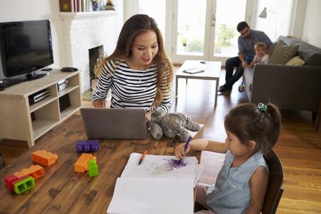 어머니는 아버지가 가정에서 아이들과 놀아 대는 동안 노트북을 사용합니다.
