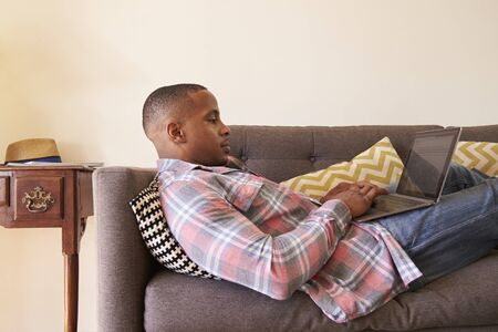 african america: Man Relaxing On Sofa At Home Using Laptop