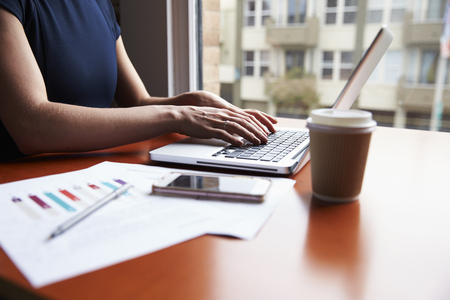 Close Up Of Businesswoman Sitting By Window Using On Laptop