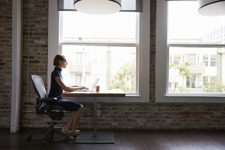 Businesswoman Sitting At Desk By Window Working On Laptop Фото со стока