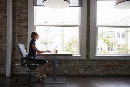 Empresaria Sentado En El Escritorio Por La Ventana Que Trabaja En La Computadora Portátil