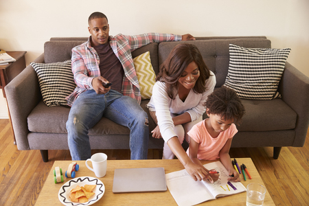 Father Watches TV As Daughter Colors In Picture Book Stock Photo