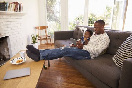 african america: Father And Son Sitting On Sofa At Home Using Digital Tablet