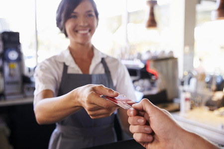 accepts: Cashier Accepts Card Payment From Customer In Delicatessen Stock Photo