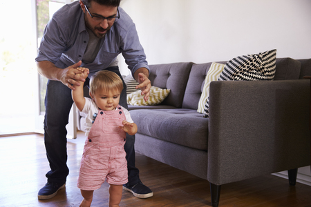 two men: Father Watching Baby Daughter Take First Steps At Home
