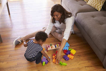 african america: Mother And Son Playing With Toys On Floor At Home Stock Photo