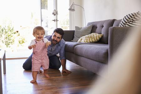 Parents Regarder Fille Bébé prendre les premières mesures à la maison