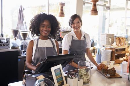 Portret van vrouwelijke personeelsleden die werkzaam zijn bij Delicatessen Afrekenen Stockfoto