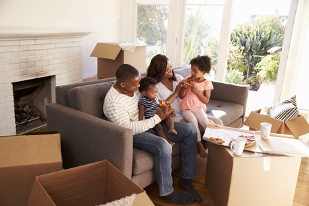 american house: Family Take A Break On Sofa With Pizza On Moving Day Stock Photo