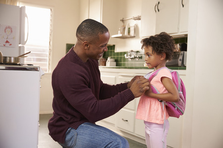 helps: Father Helps Daughter With Backpack As She Leaves For School