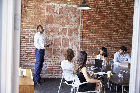 african american woman: Businessman Standing To Address Boardroom Meeting Stock Photo