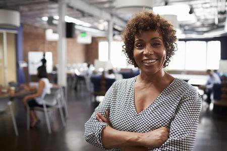 モダンなオープン プラン オフィスの成熟した女性実業家の肖像画 写真素材