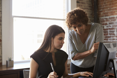 Two Businesswomen Working On Computer In Office Archivio Fotografico