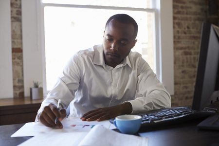 Zakenman die aan Computer in Bureau werkt Stockfoto
