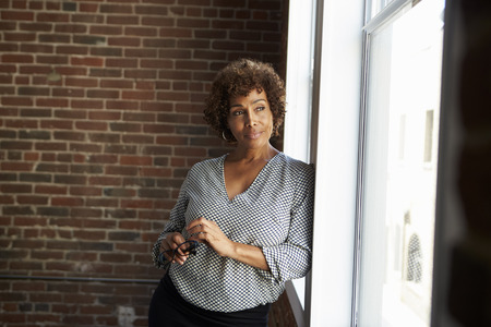 Mature Businesswoman Standing By Office Window Stock Photo