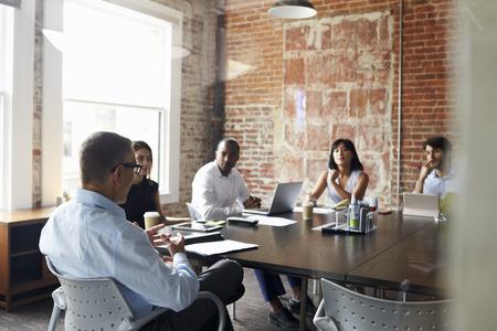 group meeting: Group Of Businesspeople Meeting In Modern Boardroom