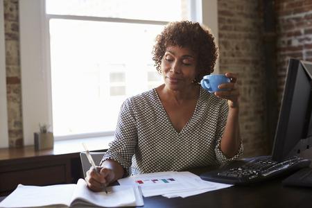 Ältere Geschäftsfrau, die im Büro arbeitet Standard-Bild