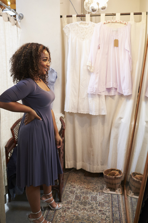 changing room: Smiling woman trying on dress in changing room, vertical Stock Photo