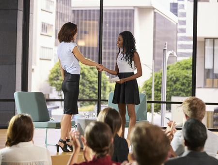 Interviewer greeting speaker on stage at a business seminar