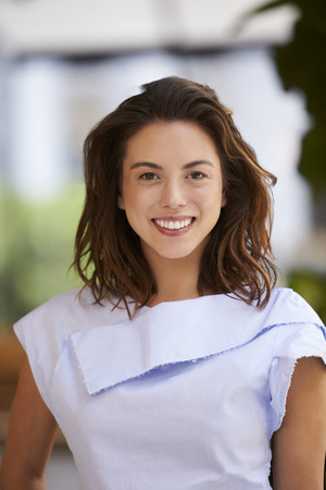 Portrait of smiling young mixed race businesswoman, vertical Stock Photo