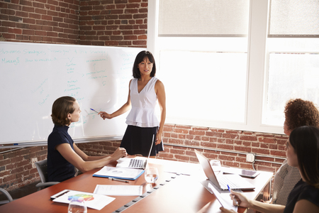 Group Of Businesswomen Meeting In Modern Boardroom Stock Photo