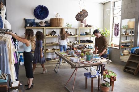 Klanten en medewerkers in een drukke kledingwinkel Stockfoto